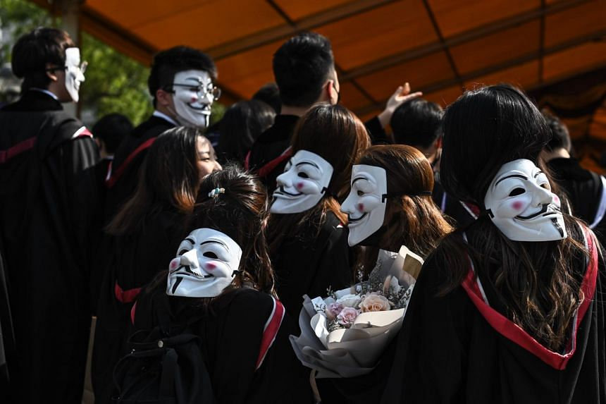 A photo of university students wearing Guy Fawkes masks in Hong Kong on Nov 7, 2019. A man holding a bouquet approached pro-Beijing lawmaker Junius Ho as the politician was campaigning in his constituency near the border with China.