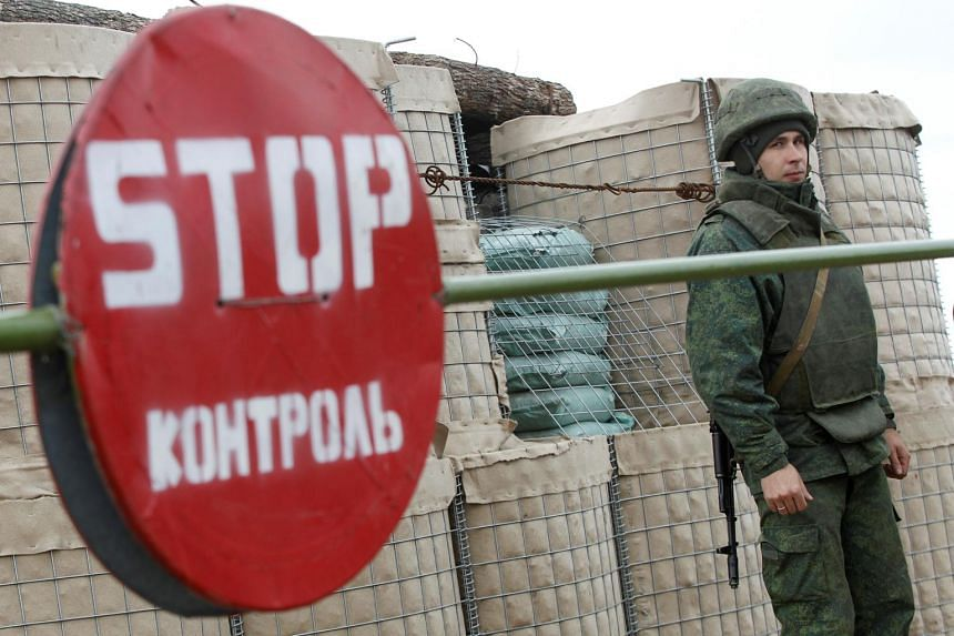 A serviceman of the separatist Donetsk People's Republic stands guard at a checkpoint in Donetsk region, Ukraine, on Nov 4, 2019.