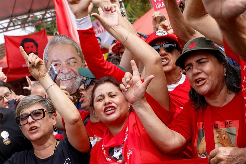 Lula supporters gesture outside the Federal Police headquarters where Lula is serving a prison sentence,Nov 8, 2019.