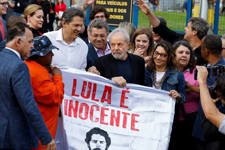 """Lula holds a banner reading """"Lula is innocent"""" after being released from prison, in Curitiba, Brazil."""