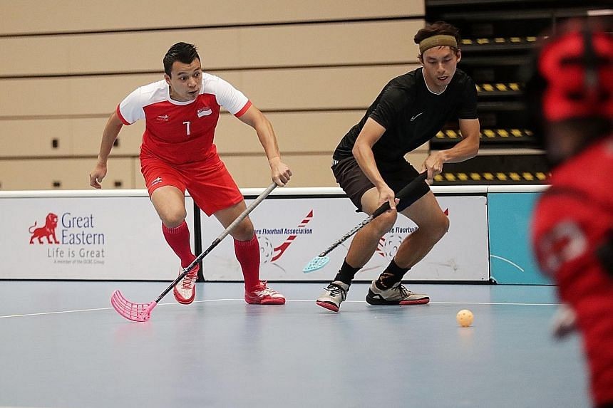 Singapore men's captain Syazni Ramlee (left) playing in an exhibition match during the SEA Games floorball jersey presentation at Our Tampines Hub yesterday.