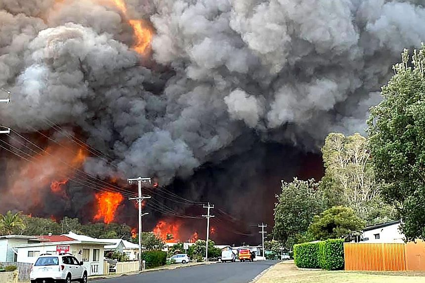 """Flames from an out-of-control bush fire as seen from a nearby residential area in Harrington, some 335km north-east of Sydney. Australian firefighters warned that they were in """"uncharted territory"""" as they struggled to contain dozens of out-of-contro"""