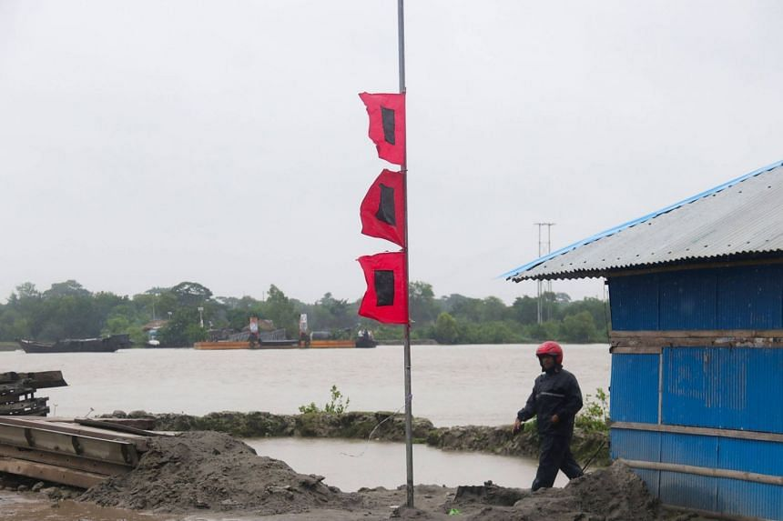 A man walking near flags that warn of storms in a village in Khulna, Bangladesh, on Nov 9, 2019.