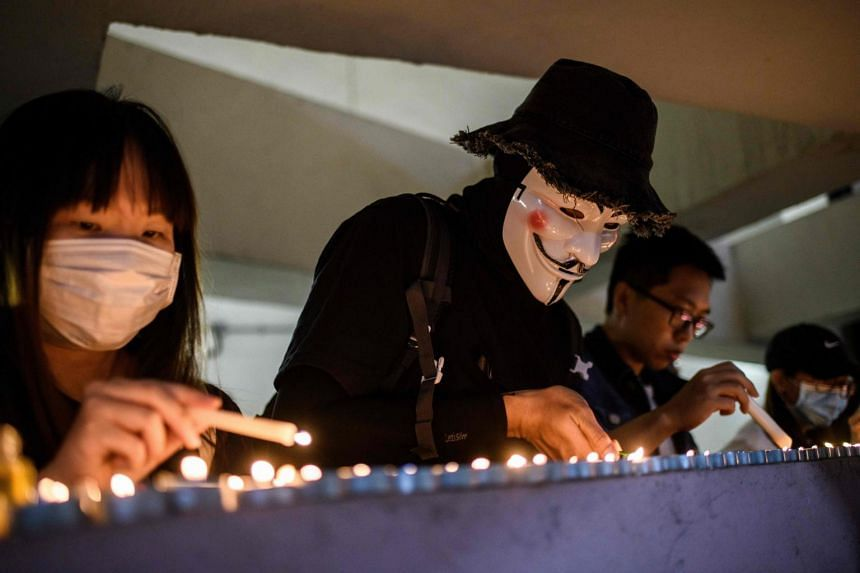 Mourners light candles in Kowloon, Hong Kong, on Nov 8, 2019, as they pay their respects at the car park where a student fell to his death earlier in the week.