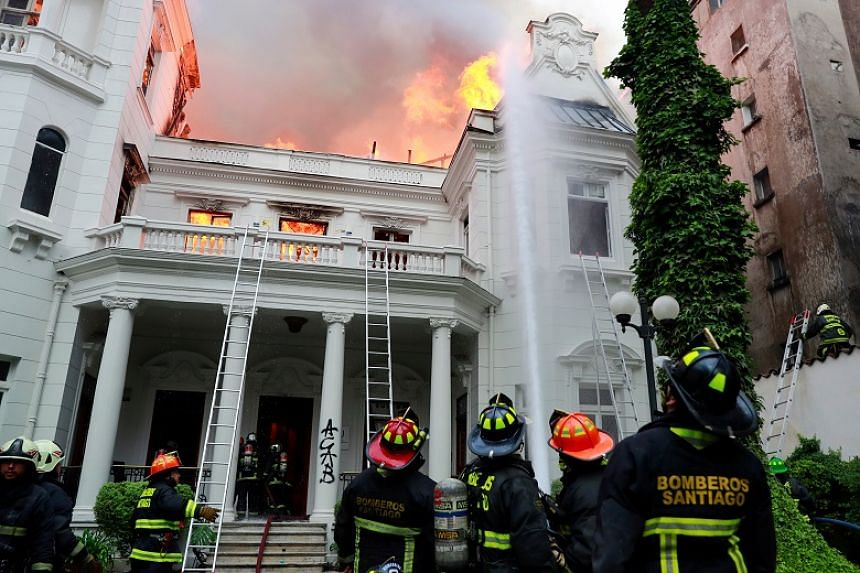 Firefighters respond to a fire at the Pedro de Valdivia University during a protest against Chile's government in Santiago, Chile, Nov 8, 2019.