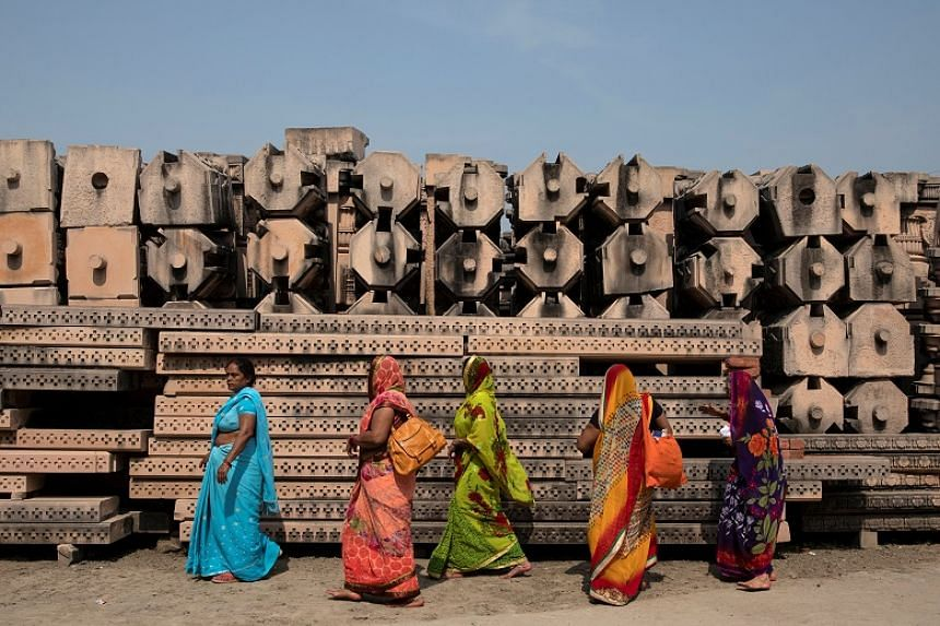 Devotees walk past the pillars that Hindu nationalist group Vishva Hindu Parishad say will be used to build a Ram temple at the disputed religious site in Ayodhya, India, on Oct 22, 2019.