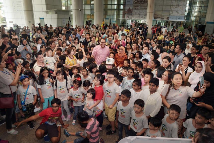 President Halimah Yacob and Minister for Communications and Information S. Iswaran (centre) at a cake-cutting ceremony with about 230 children at the National Library Building.