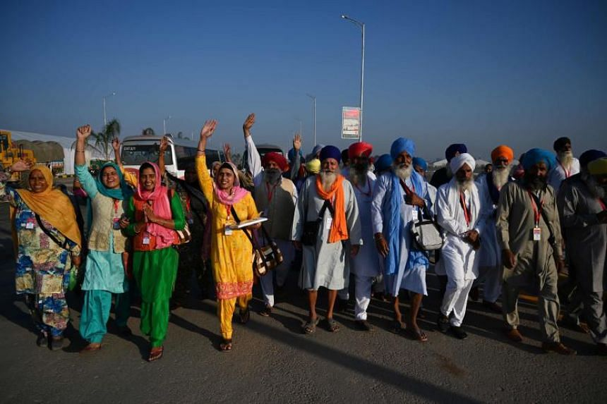 Sikh pilgrims shout slogans as they arrive to visit a shrine in Kartarpur, near the Indian border, on Nov 9, 2019.
