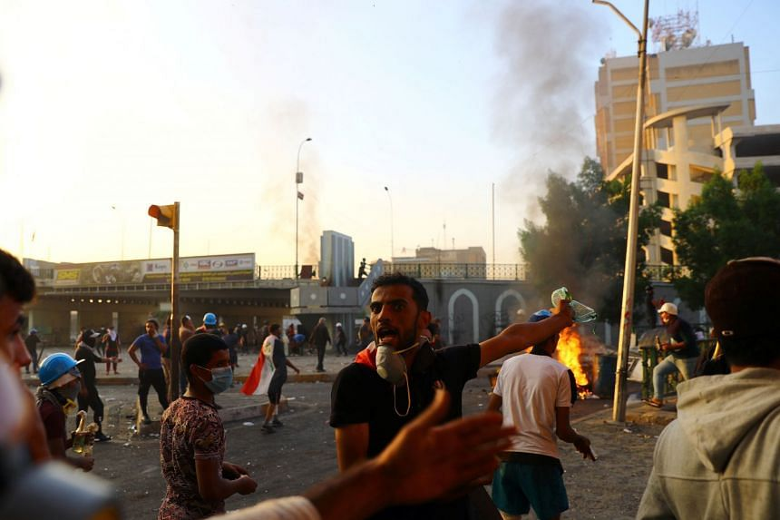 An Iraqi demonstrator reacts as protesters clash with Iraqi security forces during ongoing anti-government protests in Baghdad.