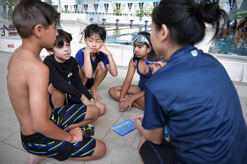 "Teacher Grace Wong, 29, leading the pupils through a reflection session after their swim in the ""polluted"" water last Tuesday. Grade 4 pupils from Gems World Academy (Singapore) took on the role of sea turtles and navigated the ""polluted"" water in th"