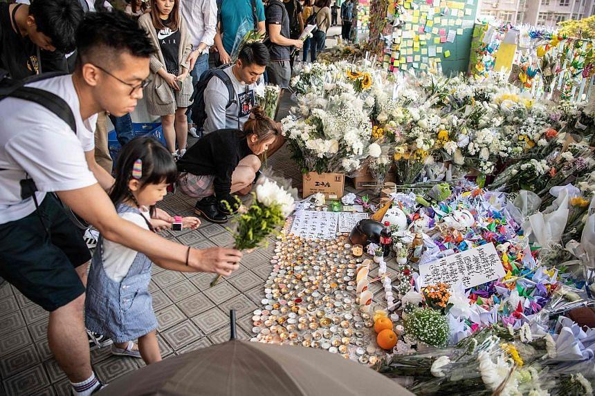 Mourners placing flowers by a makeshift memorial yesterday at the multistorey carpark where student Chow Tsz Lok, 22, fell during a recent protest in the Tseung Kwan O area in Kowloon. The death of Mr Chow is likely to fuel anger against the police, who p