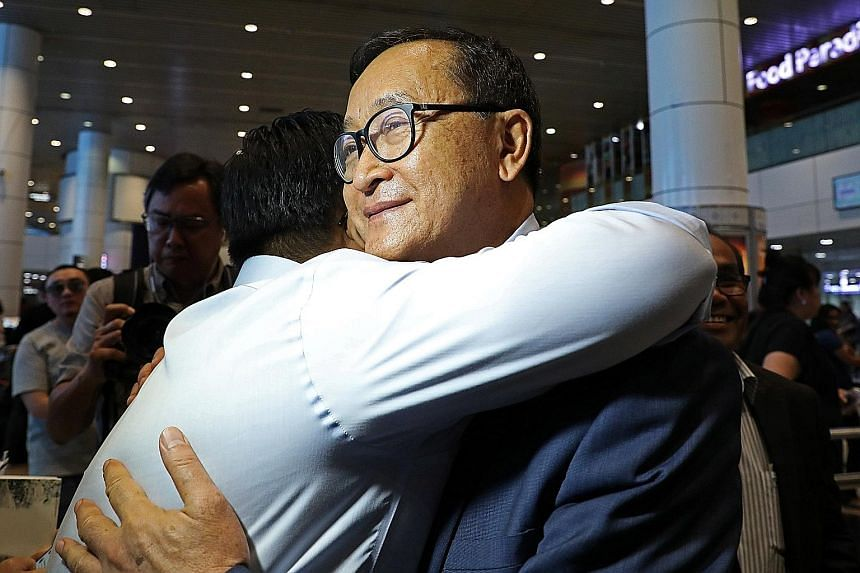 Sam Rainsy with a supporter on his arrival in Malaysia yesterday. Cambodian PM Hun Sen characterised Rainsy's plan to return home as an attempted coup against his rule of more than three decades.