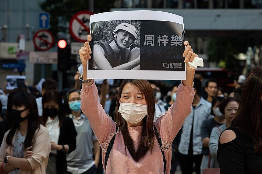 Protesters taking part in a flash mob rally in Hong Kong last Friday. They were mourning the death of Mr Chow Tsz Lok, a student who died following clashes between the police and protesters last Monday.