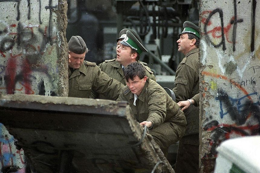 West Berliners on Nov 10, 1989, hammering the graffiti-covered remains of the Berlin Wall. But the next day, East German border guards (above) are seen fixing a section of the wall. The fall of the Berlin Wall ushered in the end of communism and Germany's