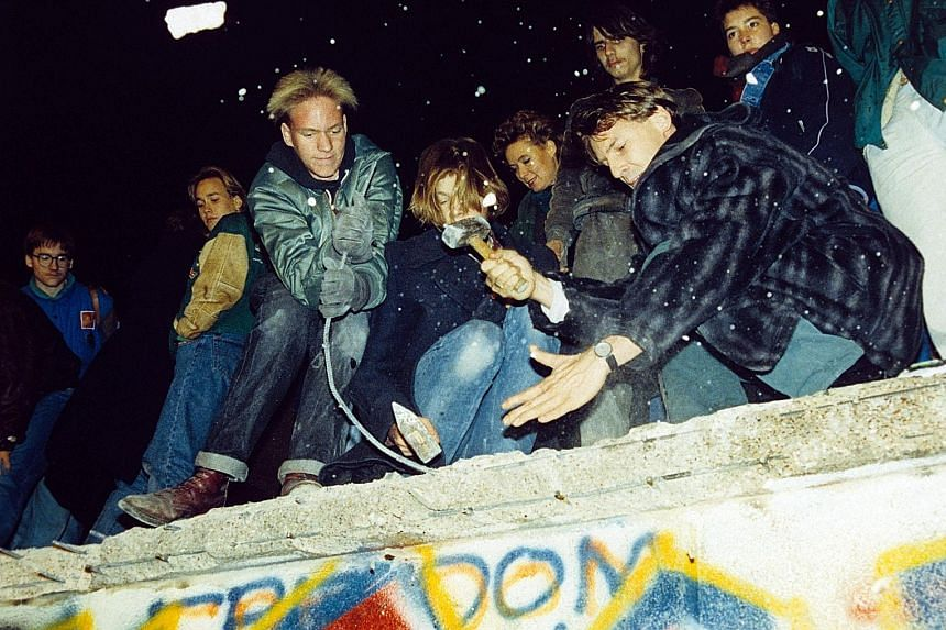 West Berliners (above) on Nov 10, 1989, hammering the graffiti-covered remains of the Berlin Wall. But the next day, East German border guards are seen fixing a section of the wall. The fall of the Berlin Wall ushered in the end of communism and Germany's