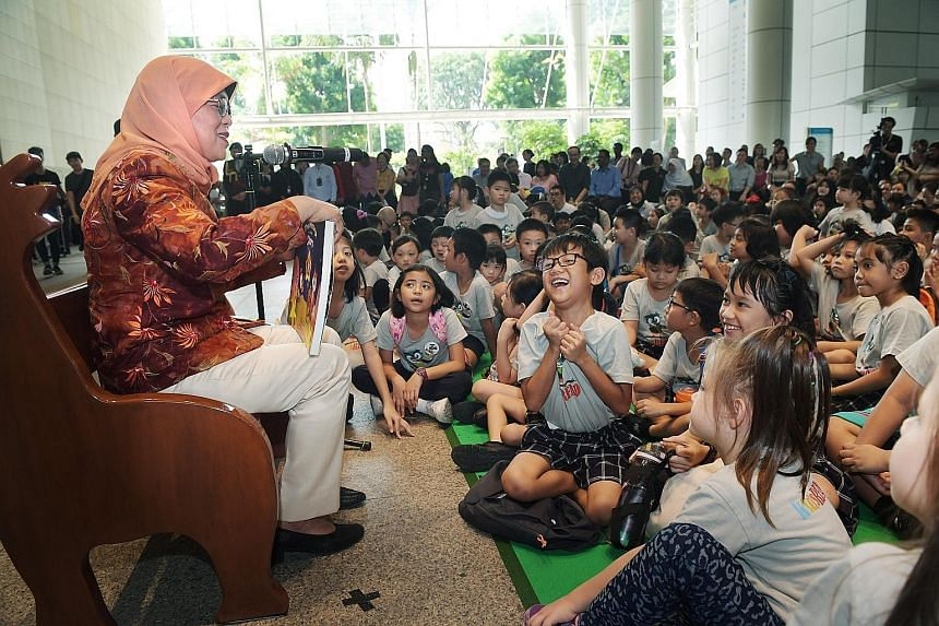 President Halimah Yacob reading a book, The Message In The Stars, to about 230 children, their parents and volunteers at the National Library in Victoria Street yesterday. ST PHOTO: ALPHONSUS CHERN