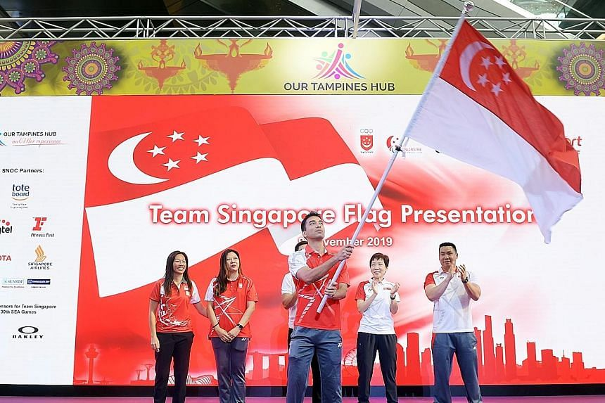 SEA Games flag-bearer Samuel Kang waving the flag at the flag presentation ceremony for Singapore athletes at Our Tampines Hub yesterday. Looking on (from left) are Winter Youth Olympics 2020 chef de mission Joanne Kyra Loo, SEA Games 2019 chef de mission