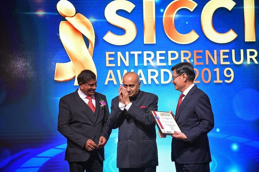 Mr Ameerali R. Jumabhoy (centre) receiving the Singapore Indian Chamber of Commerce and Industry (SICCI) Lifetime Achievement Award from Deputy Prime Minister Heng Swee Keat in the presence of SICCI chairman T. Chandroo at a dinner to mark the SICCI'