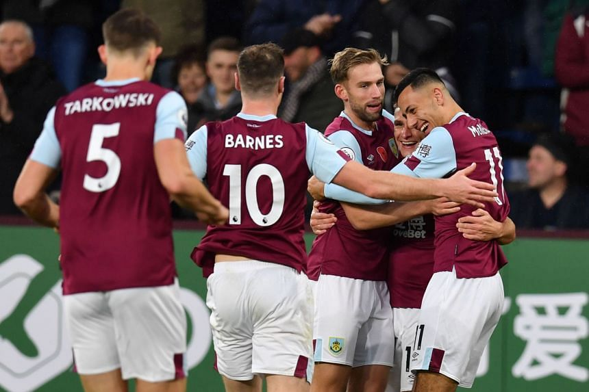 Burnley players celebrate their third goal, an own goal scored by West Ham United's Spanish goalkeeper Roberto.