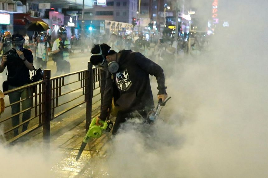 A protester uses a leaf blower to disperse tear gas during an anti-government demonstration in Hong Kong on Nov 10, 2019.