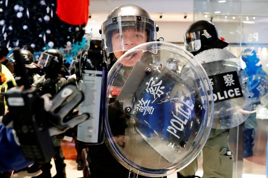 A member of the riot police holds pepper spray as he tries to disperse anti-government protesters, in Hong Kong on Nov 10, 2019.