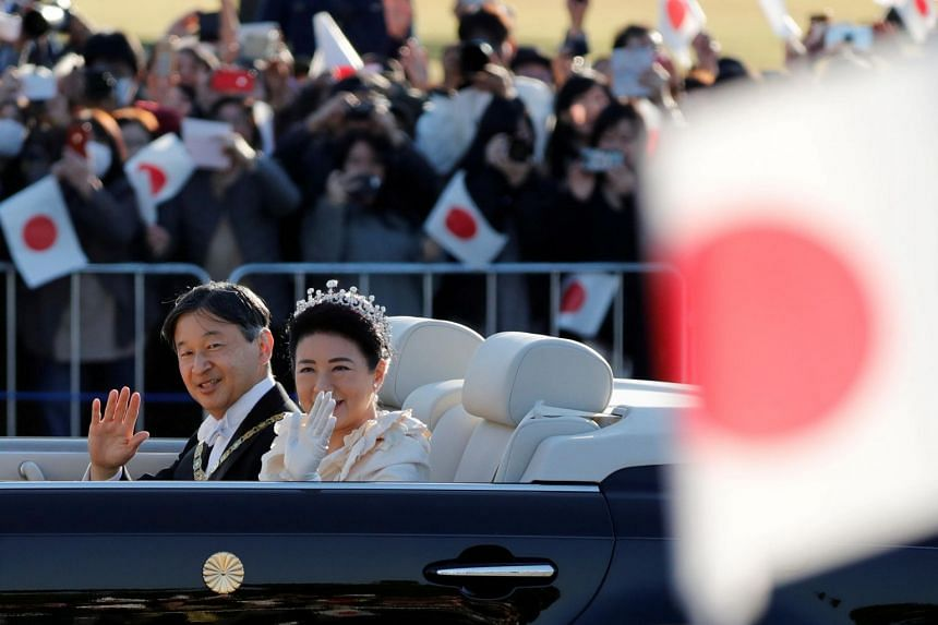 Emperor Naruhito and his wife Empress Masako wave to well-wishers during their royal parade to mark the enthronement of Japanese Emperor Naruhito in Tokyo on Nov 10, 2019.
