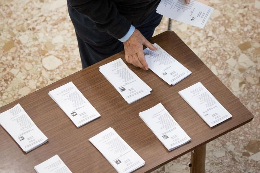 A man chooses a ballot at a polling station in Valencia, Spain, on Nov 10, 2019.