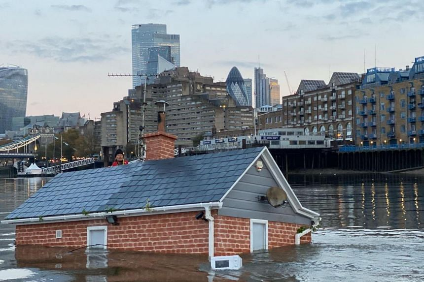 A floating mock-up of a typical British suburban home was seen slowly sinking into the Thames in a protest by Extinction Rebellion on Nov 10, 2019.