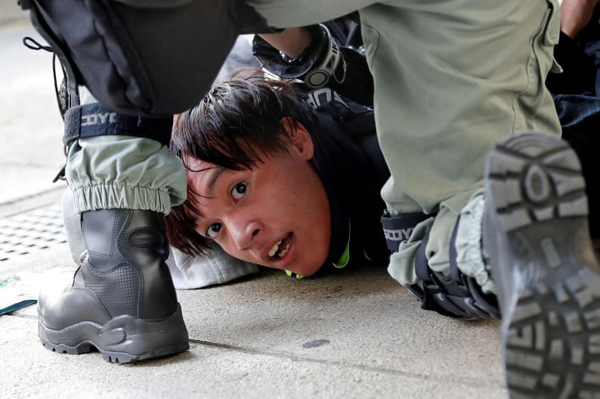 A protester is detained by riot police officers during an anti-government demonstration in Hong Kong on Nov 10, 2019.