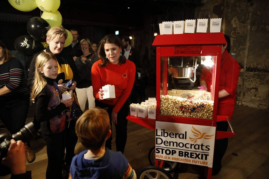 Liberal Democrats leader Jo Swinson poses serving children with popcorn after giving a speech at a general election rally in London on Nov 9, 2019.