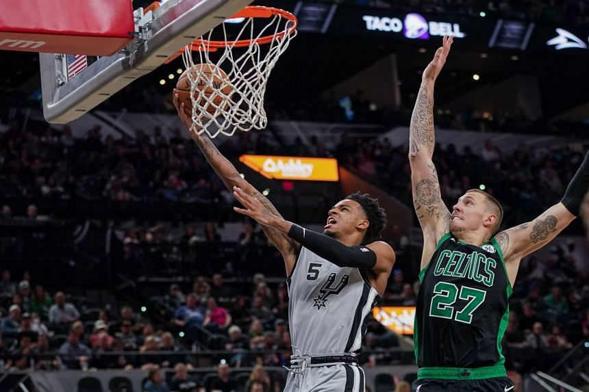 San Antonio Spurs guard Dejounte Murray (left) shoots in front of Boston Celtics forward Daniel Theis at the AT&T Center on Nov 9, 2019.