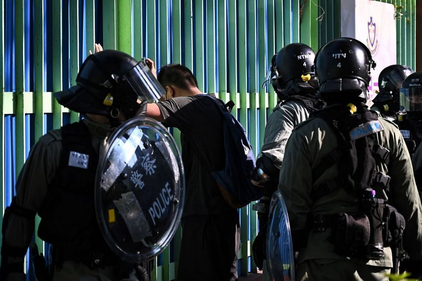 A man is detained by police during a protest in the Tuen Mun district of Hong Kong on Nov 10, 2019.