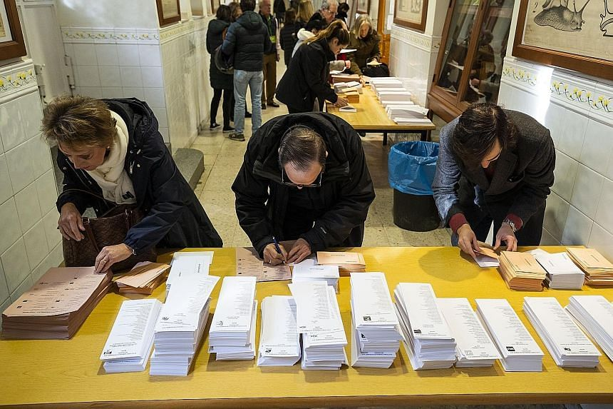 Voters collecting their voting papers at a polling station in Madrid during the general election yesterday.