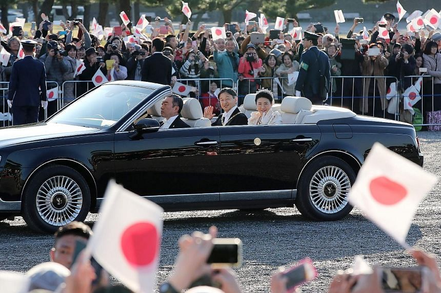 Japan's Emperor Naruhito and Empress Masako waving to the crowd during an open-top car parade in Tokyo yesterday, part of events marking the emperor's enthronement. Tens of thousands of spectators from across the country gathered along the 4.6km rout