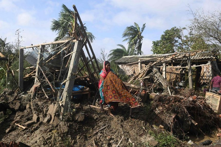 A woman beside the remains of her house in the village of Bakkhali, in India, after it was damaged by Cyclone Bulbul. PHOTO: AGENCE FRANCE-PRESSE