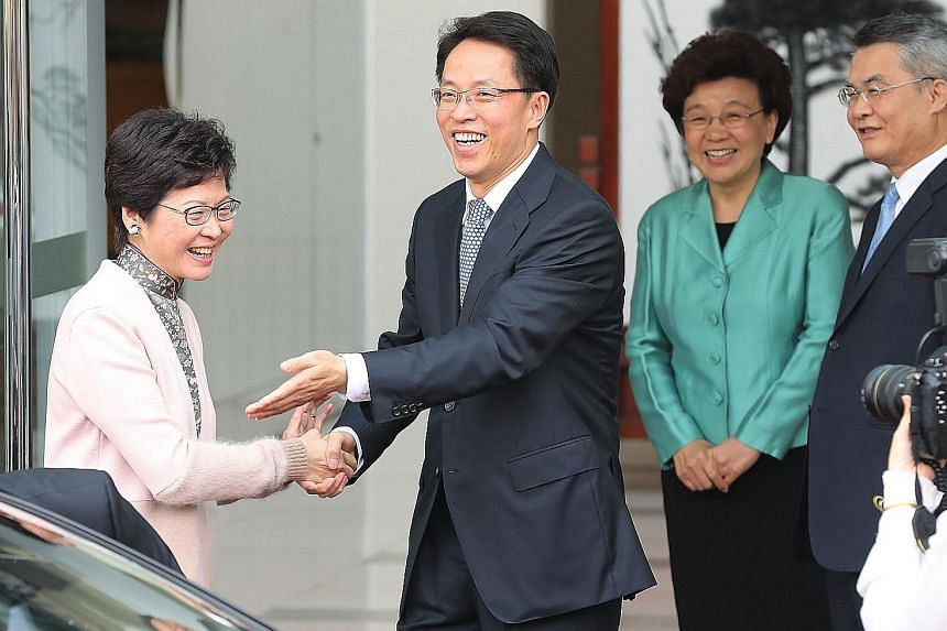 Mrs Carrie Lam shaking hands with the director of Beijing's liaison office in Hong Kong, Mr Zhang Xiaoming, in 2017. PHOTO: SOUTH CHINA MORNING POST