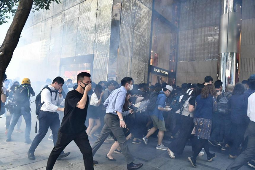 People react after tear gas was fired by police during a protest in Hong Kong, on Nov 11, 2019.