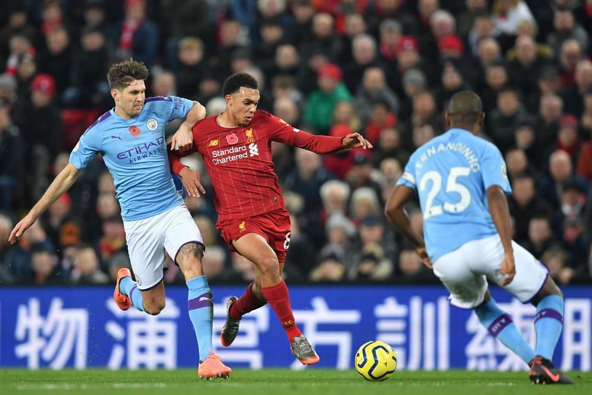 Liverpool's English defender Trent Alexander-Arnold (centre) vies with Manchester City's English defender John Stones (left) during the match, on Nov 10, 2019.
