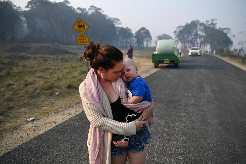 A Wytaliba resident holds her son as she waits to get back to her house at a roadblock near Glen Innes, New South Wales, Australia, on Nov 11, 2019.