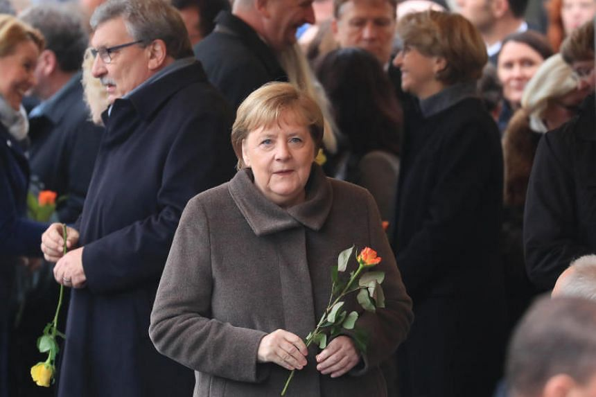 Germany Chancellor Angela Merkel arrives with a rose in her hand at a commemoration ceremony for the 30th anniversary of the fall of the Berlin Wall, in Berlin on Nov 9, 2019.