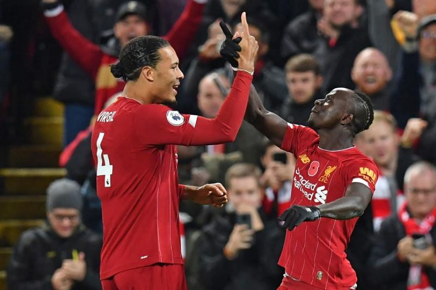 Liverpool striker Sadio Mane (right) celebrates with teammate Virgil van Dijk (left) after scoring their third goal during the English Premier League football match between Liverpool and Manchester City at Anfield in Liverpool, on Nov 10, 2019.