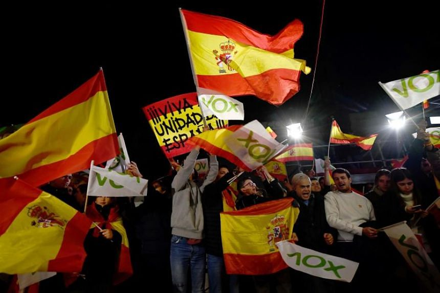 Supporters of Spanish far-right party Vox wave flags as they celebrate outside the party's headquarters during election night in Madrid on Nov 10, 2019.