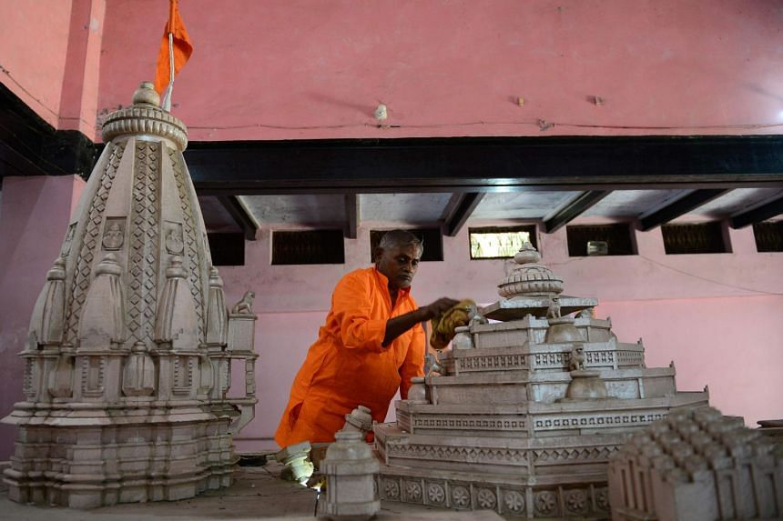 A worker cleans a model of a proposed Ram Hindu temple in Ayodhya, on Nov 11, 2019.