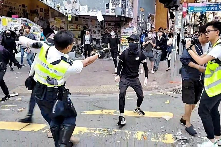 A police officer aiming his gun at a protester in Sai Wan Ho, Hong Kong, on Nov 11, 2019.