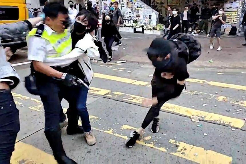 A protester tackles a police officer who was aiming his gun at another protester in Sai Wan Ho, Hong Kong, on Nov 11, 2019.