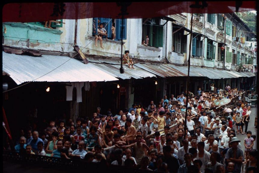 Above: A crowd watching a Chinese opera performance in Chin Nam Street, photographed by Paul Piollet in 1971.