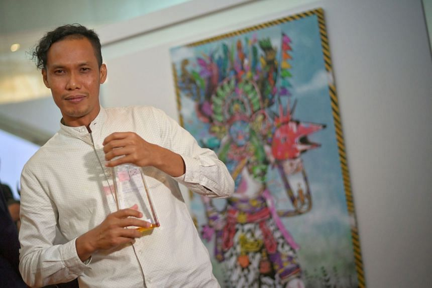 Artist Anagard with his work titled Welcome Perdamaian, Goodbye Kedengkian (Welcome Peace, Goodbye Hostility). He studied at the Indonesian Institute of the Arts in Yogyakarta.
