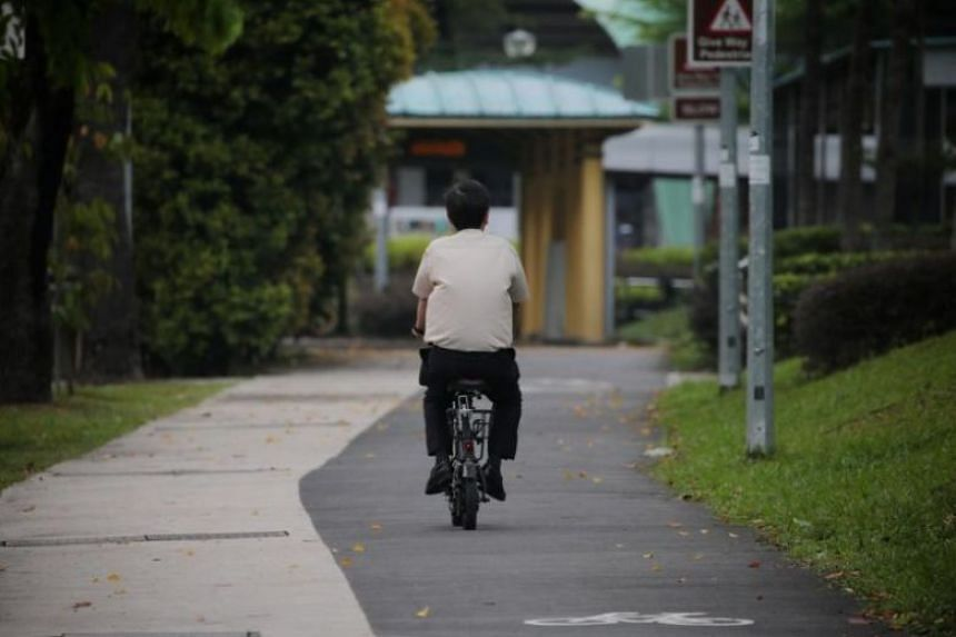 A man rides his PMD on a cycling path.