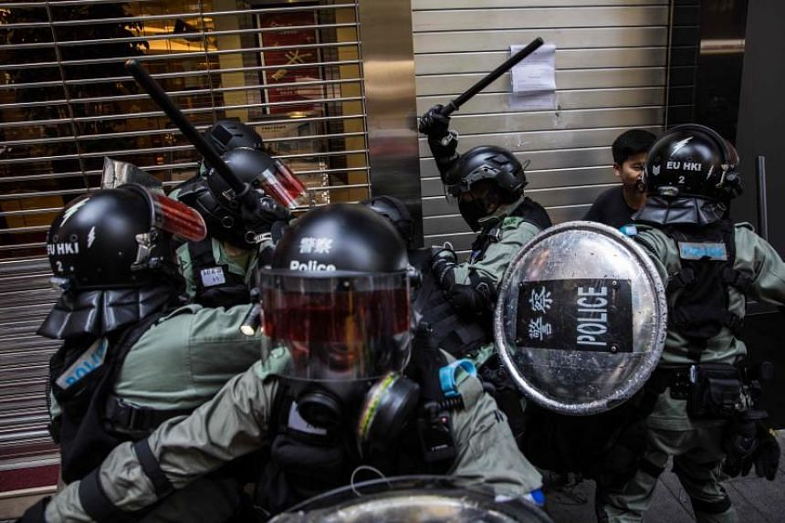 Riot police detain protesters in the Central district of Hong Kong on Nov 11, 2019.