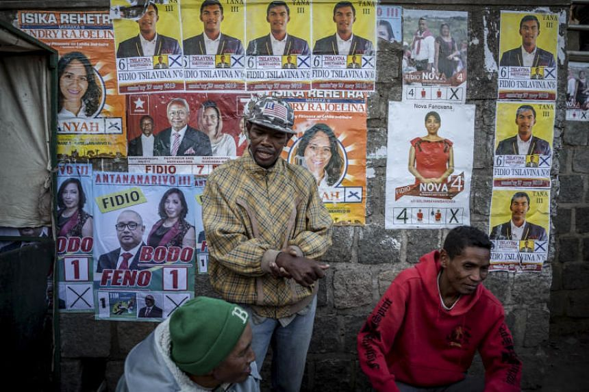 Vendors stand by a wall covered in candidate photos ahead of legislative elections in Antananarivo, Madagascar, in May 2019.